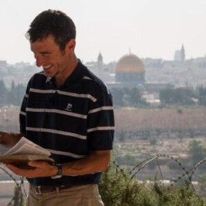 man standing with his bible open and the city of Jerusalem in the background