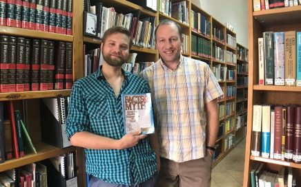 Two Caspari employees, Alec and David, in the Caspari Center library, holding a book called Facts and Myths About the Messianic Congregations in Israel