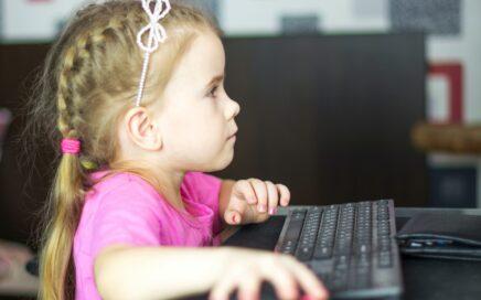 Pieni tyttö pelaa tietokoneella